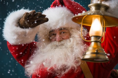 Photo for Santa Claus is holding a shining lantern while sneaking to his home outdoors at North Pole - Royalty Free Image