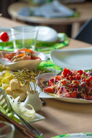 Photo for Table full of organic food - salads, cheese, tomatoes. Well decorated. Restaurant service and domestic food. - Royalty Free Image