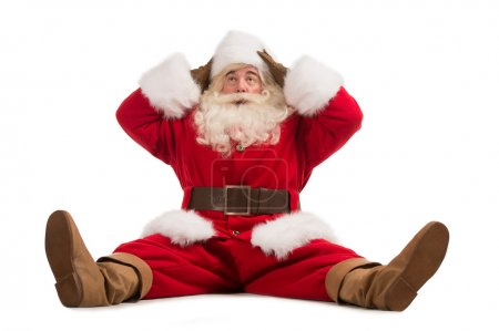 Photo for Hilarious and funny Santa Claus confused while sitting on a white background full length - Royalty Free Image