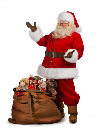 Photo for Santa Claus posing near a bag full of gifts isolated on white background - Royalty Free Image