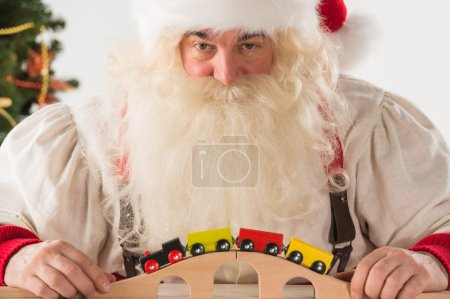 Santa Claus sitting and playing with railway toy