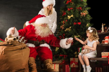 Photo for Photo of cute girl and her mother and Santa Claus at home near Christmas tree - Royalty Free Image