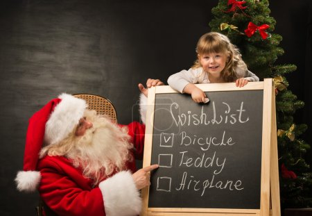 Photo for Santa Claus with child sitting near chalkboard with wish list and checking it - Royalty Free Image