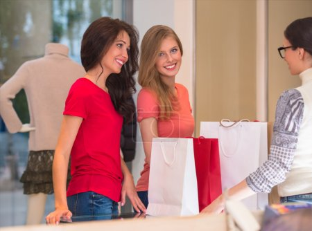 Young girls with shopping bags in store standing in front of cash