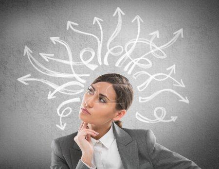 Photo pour Sérieux, jeune femme d'affaires en regardant plusieurs flèches torsadées sur le tableau de mur en béton - image libre de droit