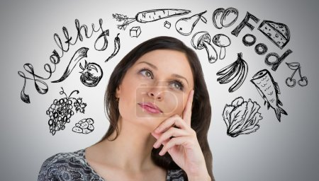 Photo for Young pretty woman thinking of healthy food closeup face portrait and sketches overhead - Royalty Free Image