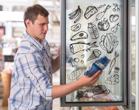 Young handsome man thinking of healthy food while shopping at grocery store
