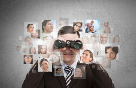 Photo for Human resources, CRM, assessment center and social media concept - business man looking for employees through binoculars. Lots of people portraits around him - Royalty Free Image