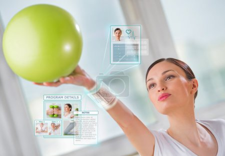 Photo for Woman doing exercise with ball wearing smart wearable device - Royalty Free Image