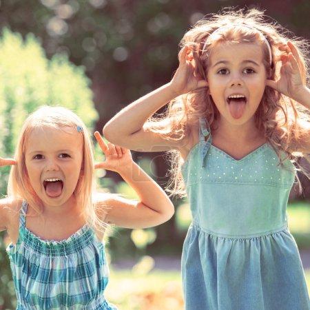 Photo pour Bonne enfance : Les petites filles s'amusent ensemble à l'extérieur dans le parc. Photo de style vintage - image libre de droit