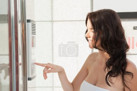 Woman dialing intercom