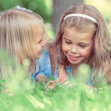 Photo pour Deux petites sœurs s'amusent dans le parc d'été tout en s'allongeant sur la pelouse. Photo filtre rétro - image libre de droit