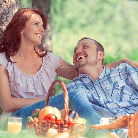 Photo pour Couple adulte pique-niquer dans le parc sous l'arbre. Photo de style rétro - image libre de droit