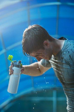 Athlete splashing  water on head