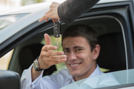 Salesman handing over keys car to businessman