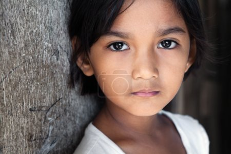 Photo for Portrait of a pretty 8 year old Filipina girl in poverty-stricken neighborhood, natural light. - Royalty Free Image