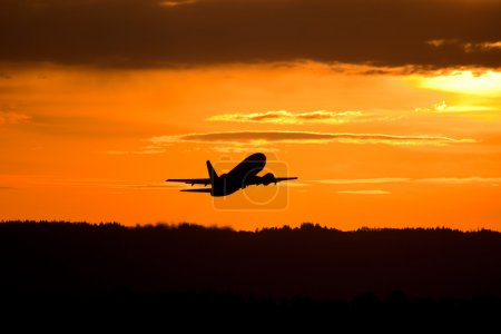 Photo for Modern commercial jet airplane - airline taking off into sunset - Royalty Free Image