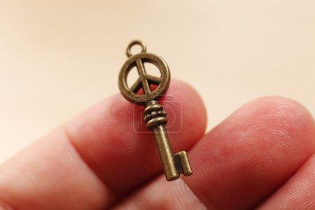 Photo pour Clés wwiwthh symbole de paix reposant sur le doigt - image libre de droit