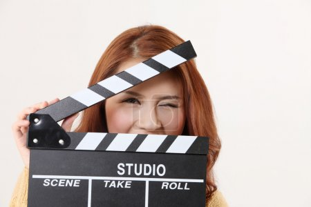 Photo for Woman hiding behind the film slate - Royalty Free Image