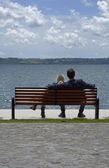 Italy, Bracciano lake - Rome, young couple relaxing on a bench