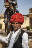 India, Rajasthan, Jaipur, indian man in traditional cloths holds is camel