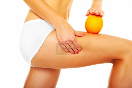 Photo for A picture of female legs and an orange over white background - Royalty Free Image