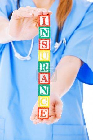 Nurse Holding Blocks Spelling Out Insurance Over White Backgroun