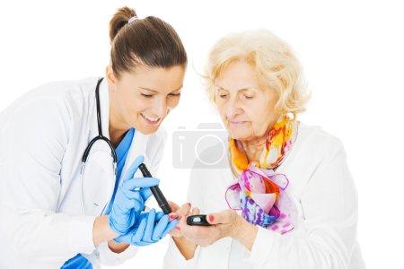 Doctor Examining Senior Woman's Blood Sugar