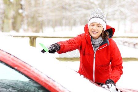 Photo pour Une photo d'une jeune femme nettoyant un pare-brise de la neige - image libre de droit