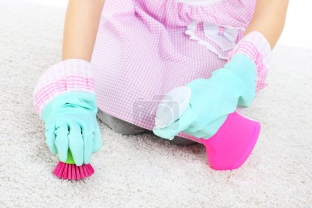 Woman cleaning stains on a carpet