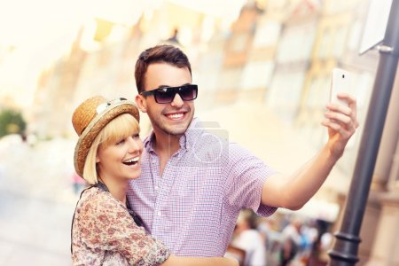 Young couple taking selfie while sightseeing the city