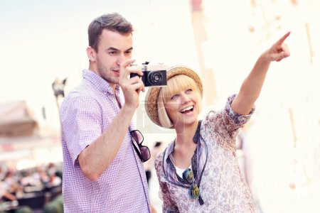 Photo for A picture of a young couple taking pictures on a tour around Gdansk in Poland - Royalty Free Image