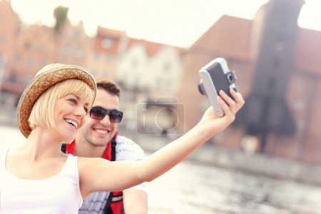 Happy couple taking pictures in a canoe