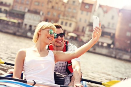 Young couple taking pictures in a canoe