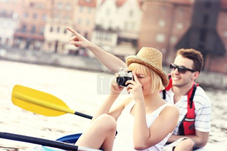 Young tourists taking pictures in a canoe