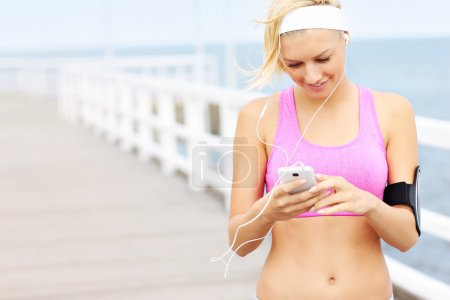 Young fit woman with phone