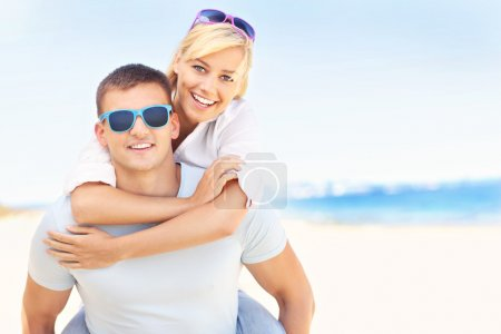Joyful couple hugging at the beach