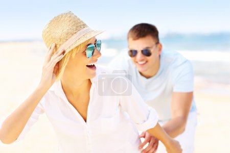 Happy man chasing a woman at the beach