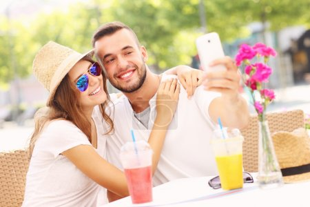 Happy couple taking selfie in a cafe