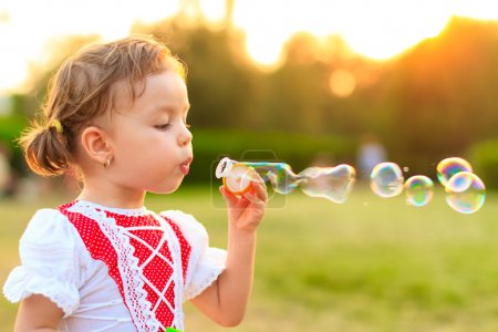Child blowing soap bubbles.