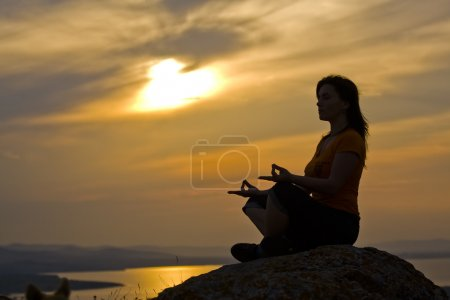 Photo for Silhouette of a beautiful woman meditating on a rock at the sunset - Royalty Free Image