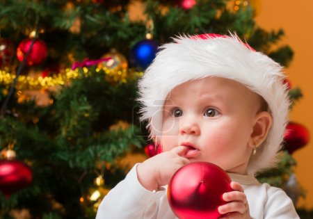 Photo for Portrait of a cheerful baby girl with red bauble and Santa hat - Royalty Free Image