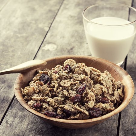 Photo for A bowl of cereal with cranberries and glass of milk on the table - Royalty Free Image