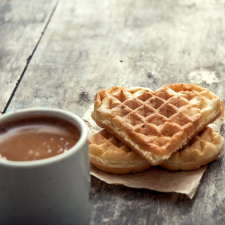 Heart shaped waffles and coffee on table...