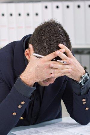 worried businessman in dark suit sitting at office desk
