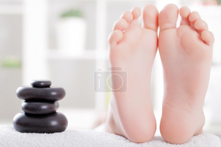 Photo for Child foot ready to spa treatment with massage stones - Royalty Free Image
