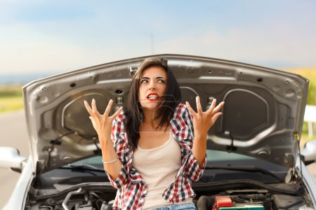 Photo for Woman being very angry because of her car's failed engine - Royalty Free Image