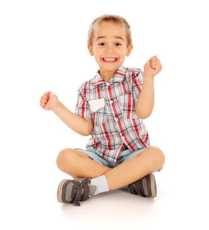 Photo pour Très excité petit gars assis et acclamant - image libre de droit