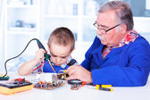Dědeček učí vnučka s páječkou
