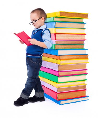 Photo for Little wise boy reading book near big stack of colorful books - Royalty Free Image
